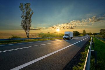 Fotobehang - White delivery van driving on asphalt road around farm fields in rural landscape at sunset