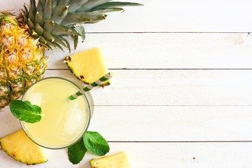 Glass of pineapple juice with fruit. Top view, side border on a white wood background.