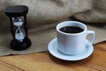 coffee time, coffee mug and an hourglass on the table