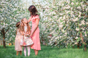 Family in blooming apple garden outdoors