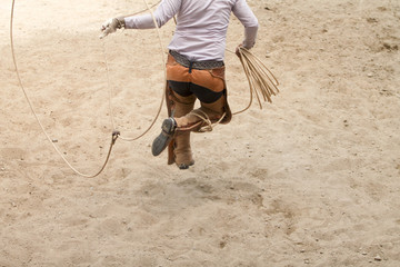 mexican charro jumping through his lasso, charreria, charreada