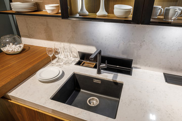 Stylish kitchen with tableware and sink on elegant wooden counter