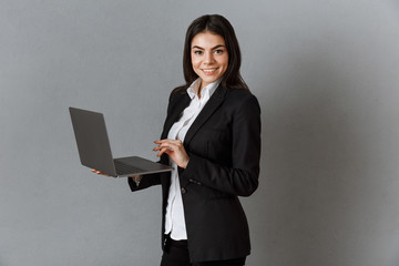 side view of smiling businesswoman with laptop against grey wall background