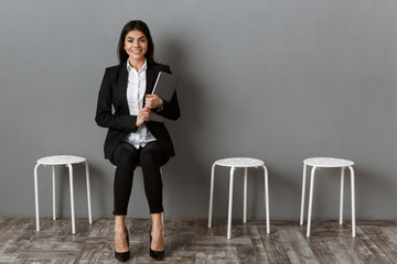 smiling businesswoman in suit with laptop waiting for job interview