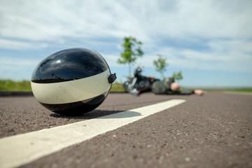 biker helmet lies on street near a motorcycle accident