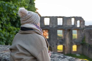 Frau vor der Burgruine Landskron in Oppenheim im Sonnenaufgang