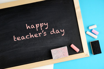 Happy teacher's day concept with a black board, chalks, note book, pen