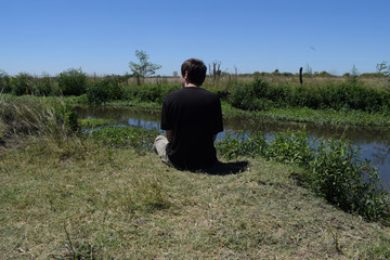 a young man on the shore of a wild river