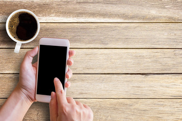 Mockup image of female hand using smartphone beside of white cup coffee