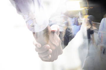 Business handshake double exposure and walking street.
