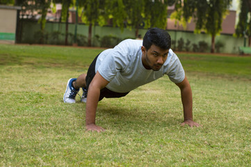Young guy doing push ups in a park
