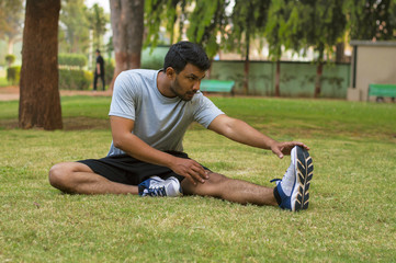 Young guy doing stretching exercise in a park