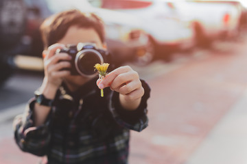 Young boy taking photos of yellow flower in his hand on vacation