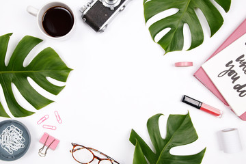 Women's home office desk workspace with tropical palm leaf, vintage camera, glasses, coffee cup, lipstick and notebook on white background. Flat lay, top view woman blog mock up. Creative concept.