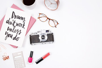 Women's home office desk workspace with handwritten quote notebook, retro camera, smartphone, lipstick and coffee cup on white background. Flat lay, top view. Creative stylish blogger concept.