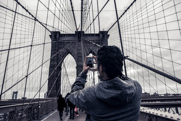 Coceptual cinematic photography tourist man taking picture with cell phone on Brooklyn Bridge, New York City