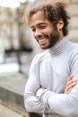 Portrait of half african male person wearing grey turtleneck sweater and having curly brown hair. Concept of fashionable look.