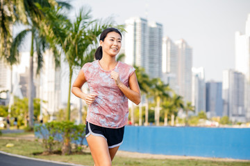 Beautiful smiling Asian woman doing morning exercises. Skyscrappers on a background