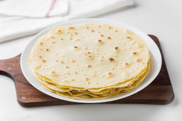 Mexican corn tortillas on a white plate on a wooden board. They can be used to make a burrito, takos and quesadilla.