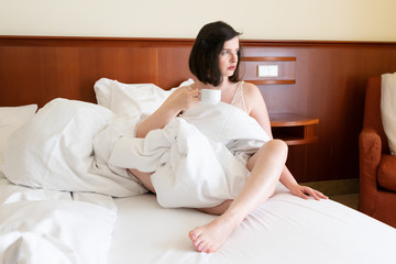 Beautiful caucasian woman sitting in a hotel bed with a cup of coffee - morning of the bride