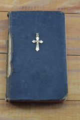 Christian cross with the old holy Bible on the table