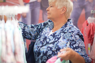 Elderly woman grandmother choosing baby clothes in the shop.