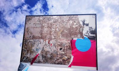 Plakatwand mit abgerissenem Plakat in blauem Himmel
