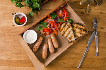 Top view, close up. Grilled sausages with vegetables, tartar sauce on wooden box on gray background. Pepper, tomato, onion, garlic and greens are served nicely on a plate. Restaurant kitchen