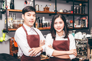 Portrait of couple barista working and standing behind the counter bar in a cafe