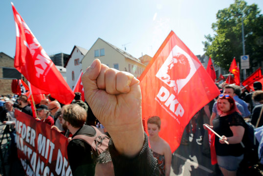 A member of the German Communist Party (DKP) raises his fist as he attends the unveiling ceremony of the 4.4 metres (14 feet) high bronze statue of Karl Marx, in Trier