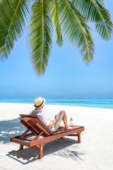 Wall Mural - Junger Mann entspannt auf einer Strandliege im Urlaub