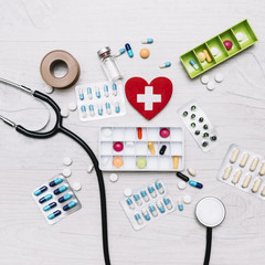 Heart with cross near stethoscope and medications