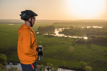 Cyclist at sunset in the mountains. A young man in a helmet and glasses drinks water from a bottle.
