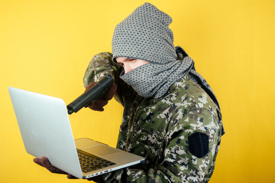 Portrait of a hacker man terroris in a camouflage and a mask is looking at the laptop. the concept of anonymity and terrorism hacking the system.