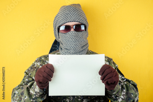 a terrorist man in a camouflage, glasses and a mask holds a