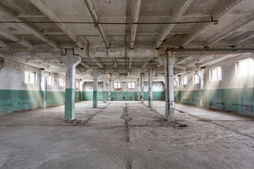 Industrial warehouse with cement walls, floors, windows and pillars before construction, remodeling, renovation, extension, restoration, reconstruction. Industrial background.
