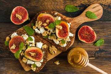 Healthy toasts with rye bread, fresh figs, honey, walnuts, mint leaves and cheese on the wooden board, top view