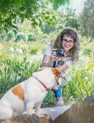 Young happy smiling woman photographer taking a photo of sitting small dog jack russel terrier outside in green summer park at sunny day.