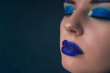 Portrait of a beautiful girl with a blue make-up and sparkles on her lips