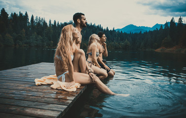 Group of friends having fun at the lake in the morning