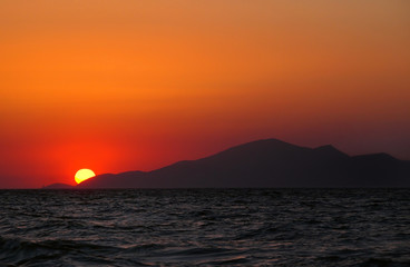 beautiful mediterranean sunset over over the island of kos with an orange evening sky and light reflected in a dark calm sea