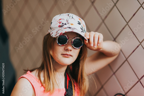 168700bf895a Outdoor portrait of cute little preteen girl wearing fashion cap and  sunglasses
