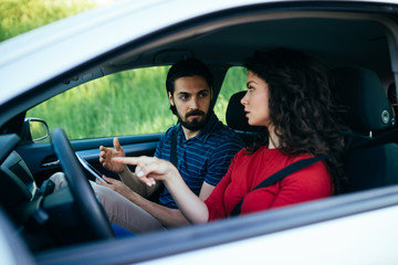 Driving school or test. Beautiful young woman learning how to drive car together with her instructor.