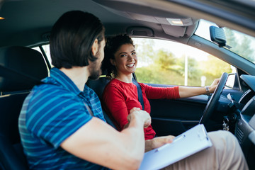 Driving school or test. Beautiful young woman learning how to drive car and handshaking with her instructor.