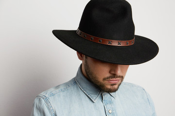 Portrait of a pensive caucasian man in hat wearing denim shirt and looking down isolated on white background