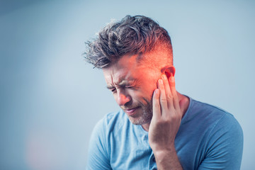 Fototapeta male having ear pain touching his painful head isolated on gray background