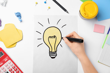 Woman drawing light bulb on white background. Business trainer concept