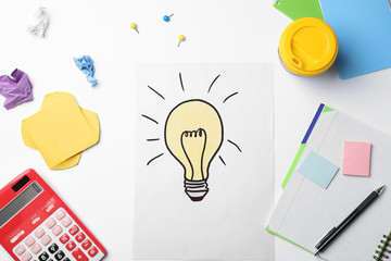 Workplace with drawing of light bulb and stationery on white background. Business trainer concept