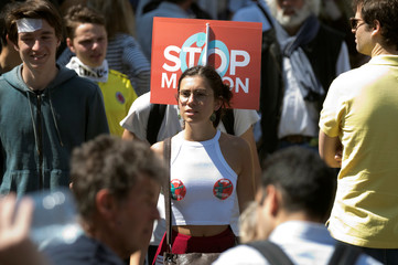 """A protester carries a placard which reads """"Stop Macron"""" during an anti-Macron """"festive"""" protest in Paris"""