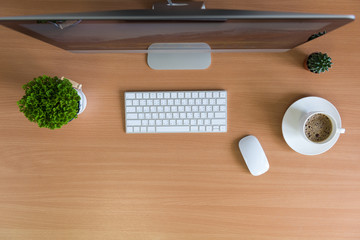 All in one computer, mouse, keyboard, cactus and plant vase  on wooden table. Flat lay style